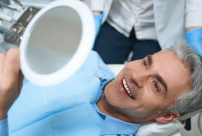 Joyful male is lying in chair and looking into mirror while being delighted with dentist work
